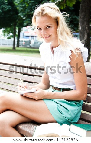 Young and beautiful female student preparing for exams in the park - stock photo