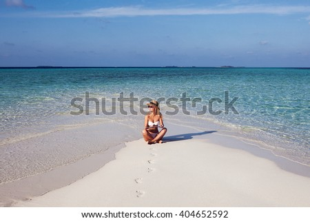 Young and beautiful girl have a seasonal winter vacation on the beach in exotic country - stock photo