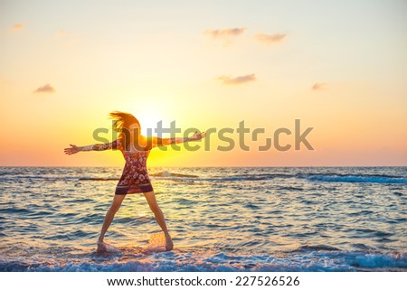young and beautiful girl in colorful dress jumping like a star in ocean water in sunset