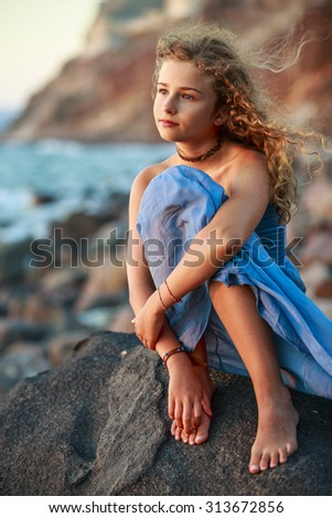 Young and beautiful girl on the beach at sunset - Santorini, Greece - stock photo