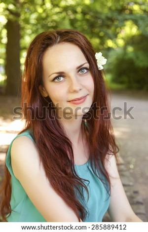 Young and beautiful girl. Portrait of smiling girl. The girl with the Jasmine flower. The girl in chiffon dress. Young woman. The red-haired girl with blue eyes. Forest nymph. - stock photo