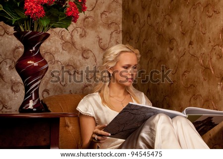 Young and beautiful girl reading a book cover in black sitting on a couch in his home