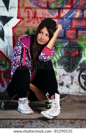 Young and beautiful girl sitting on skateboard against wall with graffiti
