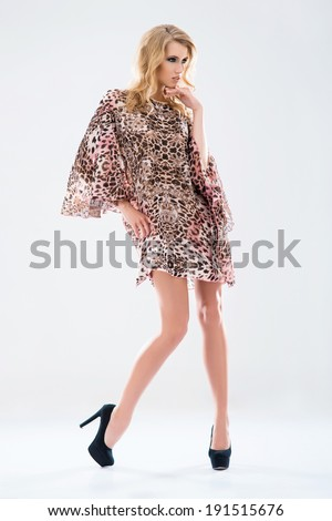 Young and beautiful model girl posing in studio in fashion summer dress  - stock photo