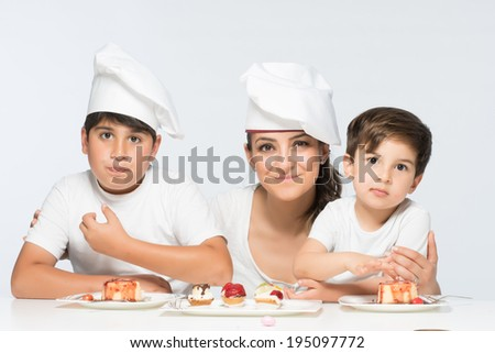 Young and beautiful mother chef with her two son in kitchen and with delicious fruit dessert dishes - stock photo