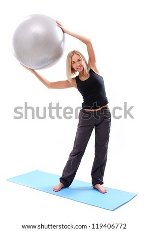 Young and beautiful woman doing exercise with fitness ball lying on a blue mat - stock photo