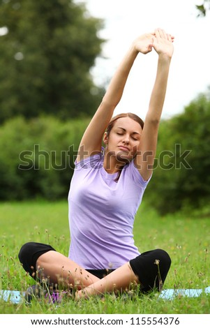 Young and beautiful woman doing her yoga workout in the park - stock photo