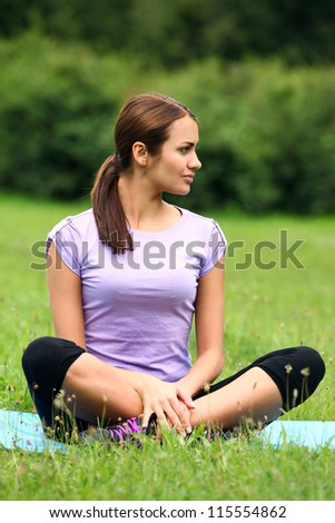 Young and beautiful woman doing her yoga workout in the park