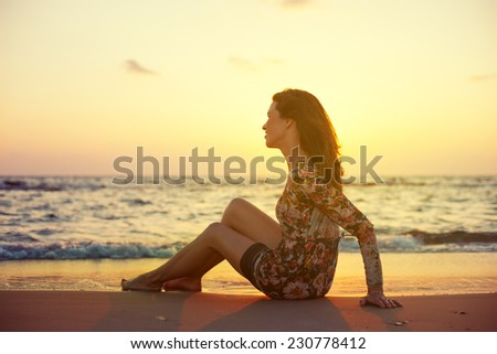 young and beautiful woman in colorful dress sitting on the sand near the ocean and looking far away at the sunset - stock photo