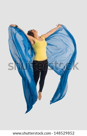 Young and beautiful woman is jumpng with wing shaped blue silk cloth