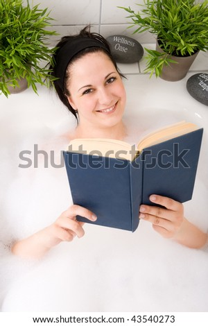 Young and beautiful woman reading a book in the bathtub - stock photo