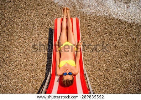Young and beautiful woman relaxing and having sunbath on the red sunbed in the sea. Top view with wide angle - stock photo