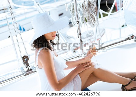 Young and beautiful woman relaxing on a luxury sailing boat at summer
