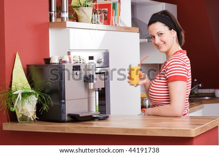 Young and beautiful woman standing in the kitchen with orange juice - stock photo