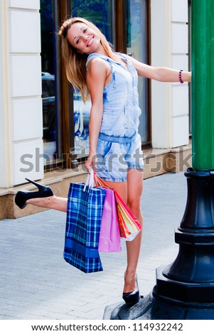 Young and beautiful woman walking down the street with shopping bags in - stock photo