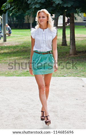 Young and beautiful woman walking in the park - stock photo