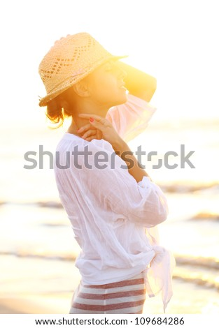 Young and beautiful woman wearing a hat in sunset light - stock photo