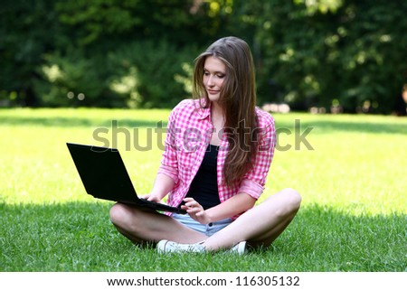 Young and beautiful woman with laptop in park