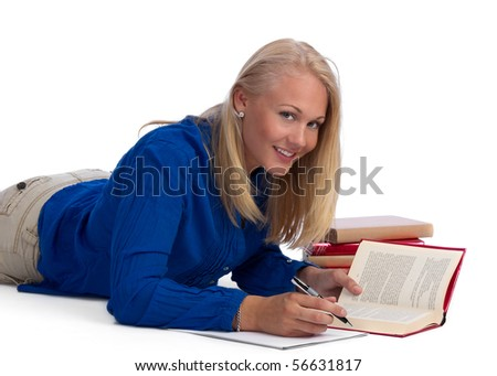 Young and blond beautiful student doing her homework, lying on the floor, smiling at the camera, on white background