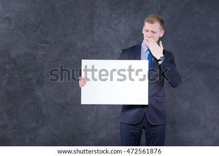 Young and bored elegant man in suit, holding a piece of paper and covering his mouth by a hand