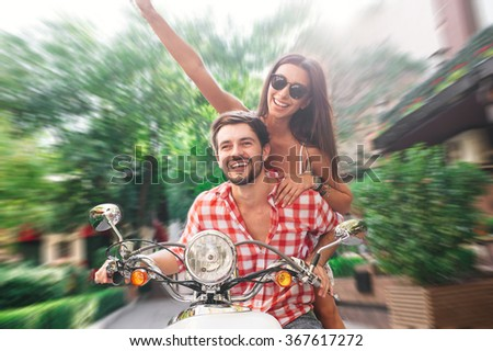 Young and carefree. Beautiful cheerful young couple smiling and riding a classic scooter together - stock photo