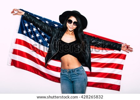 Young and carefree. Beautiful young mixed race woman carrying American flag and smiling while standing against white background  - stock photo