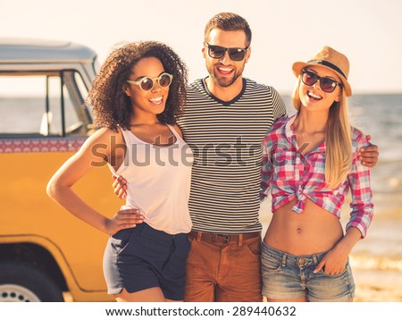 Young and carefree. Cheerful young man embracing two women while standing at the seaside with retro minivan in the background - stock photo