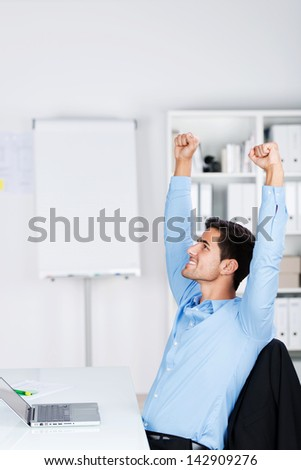 Young and cheerful businessman raising his arms in the air inside office celebrating after making a successful deal or project. - stock photo