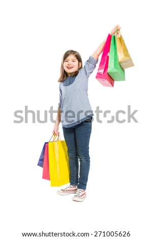 Young and cheerful shopping girl with shopping bags on white background - stock photo