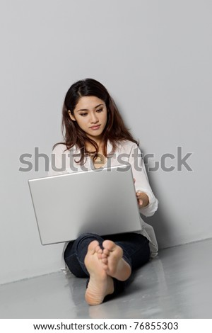 young and confident asian woman using a laptop - stock photo