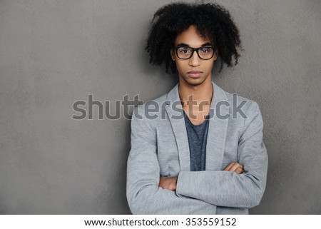 Young and confident. Confident young African man keeping arms crossed and looking at camera while standing against grey background - stock photo