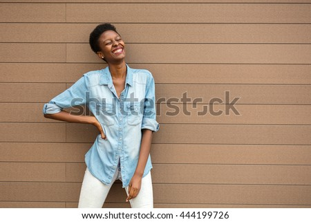 young and cool black woman standing on a wooden background, wearing a jeans shirt, empty space on her side