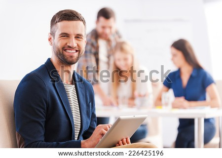Young and creative. Handsome young man holding digital tablet and smiling while his colleagues discussing something in the background - stock photo