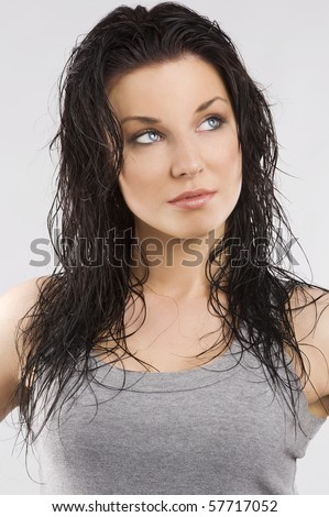young and cute brunette wearing a gray t-shirt and taking pose with wet hair and looking up - stock photo