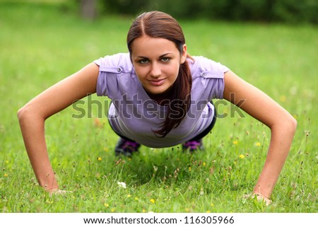 Young and cute sporty girl do her push-ups exercises in the park on a green lawn - stock photo