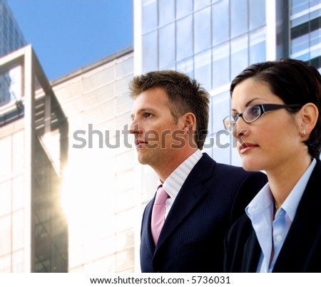 Young and determined business people looking away and posing in front of an office building. Selective focus is placed on the man's face. - stock photo