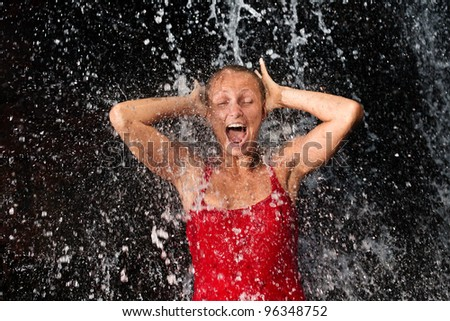Young and emotional girl in red tank-top enjoying jungle waterfall