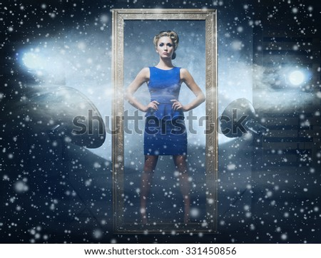 Young and emotional woman in fashion dress in frame over glamour background with snowflakes(photo studio backstage). - stock photo