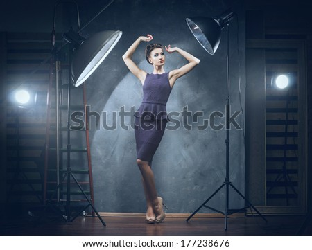 Young and emotional woman in fashion dress over glamour background (photo studio backstage) - stock photo