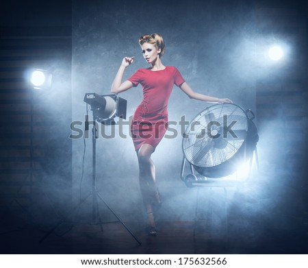 Young and emotional woman in fashion dress over glamour background (studio backstage) - stock photo
