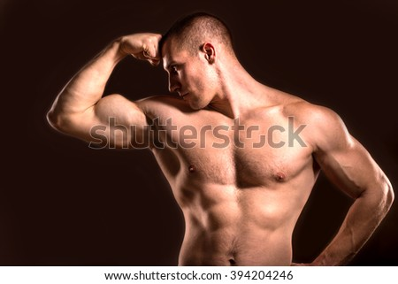 young and fit bodybuilder man model posing his muscles, dark background
