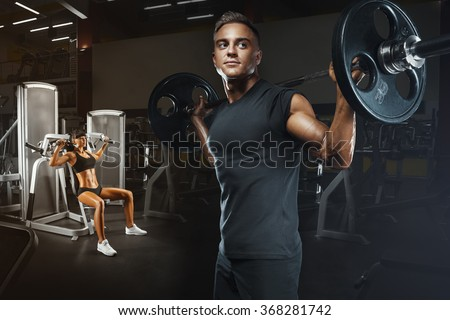 Young and fit couple in the gym doing workout. Group of women and men bodybuilders training on special sport equipment in the gym. Sport, bodybuilding, lifestyle and people concept. - stock photo