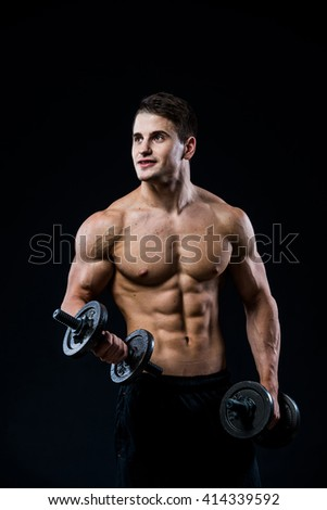 Young and fit male model posing his muscles pumping up with dumbbells in a gym looking to the left isolated on black background.