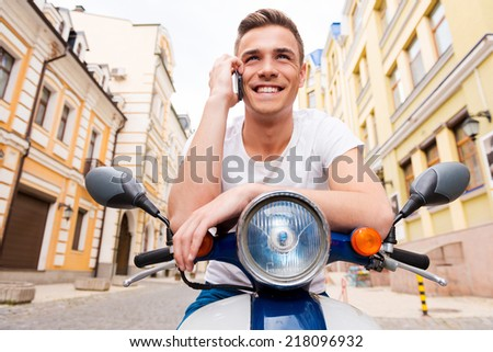 Young and free. Cheerful young man sitting on scooter and talking on the mobile phone  - stock photo