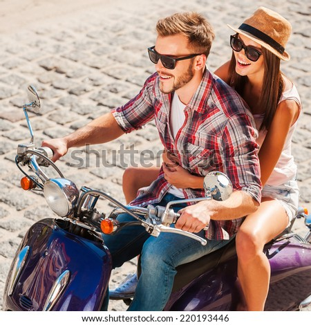 Young and free. Top view of beautiful young couple riding scooter together while happy woman bonding to her boyfriend and smiling - stock photo
