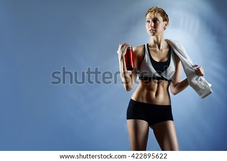 Young and fresh. Horizontal portrait of a stunning sexy woman wearing sports top and shorts posing with a bottle and a towel copyspace on the side - stock photo