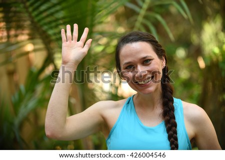Young and friendly woman waving with a greeting - stock photo