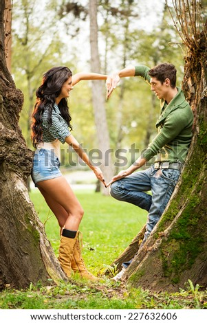 Young and good-looking girl and guy at park leaning against a tree trunk, facing each other with their hands straight form the heart. - stock photo