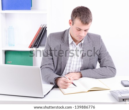 Young and handsome businessman in his office working and looking at the diary