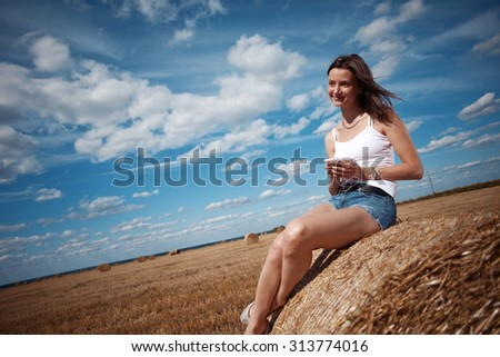 Young and handsome girl in white shirt sitting on haystack with phone